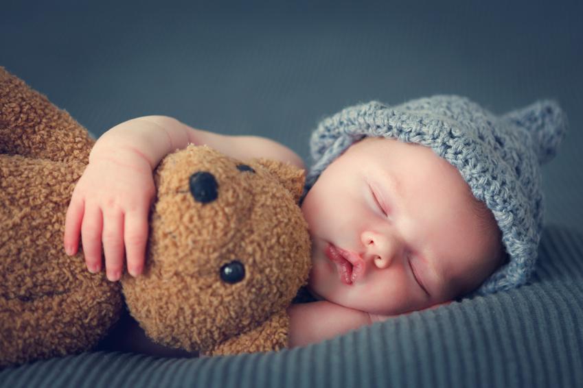 sleeping newborn baby on a blanket with a teddy